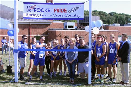 Cross country team with Ryan Coleman, Coach Bahn, and Mark Czapp in front of ribbon at the start banner.