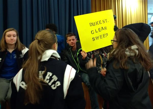 students hold sign that says duke street clean sweep