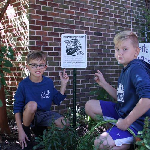 NSE Students point to the Monarch Waystation sign